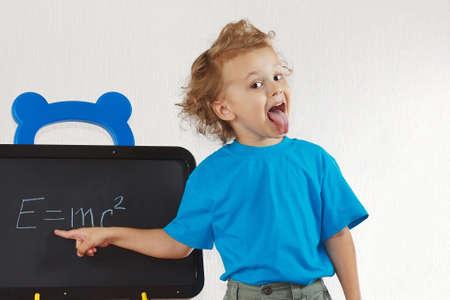 Little boy shows tongue like Einstein near formula on a blackboard photo