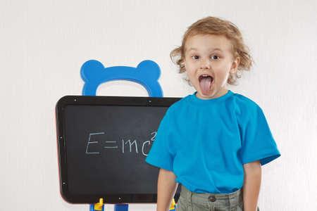 Little boy shows tongue as Einstein near formula on a blackboard photo