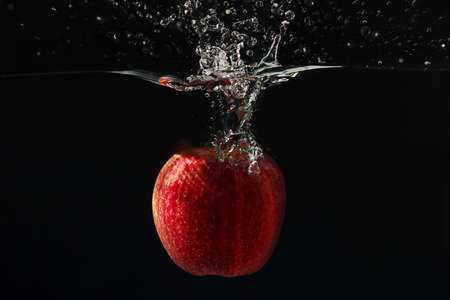 Red apple falling into the water with a splash on a black background closeup photo
