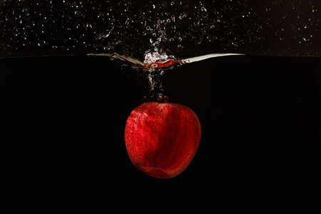 Red apple falling into the water with a splash on a black background closeup