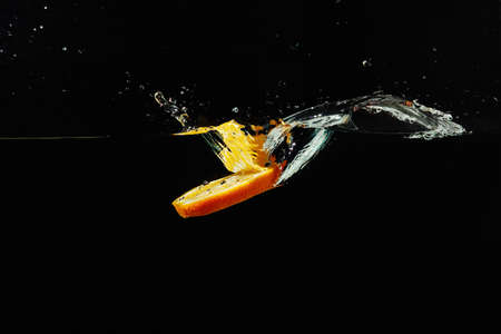 Sliced fresh orange falling into the water with a splash on a dark background closeup photo