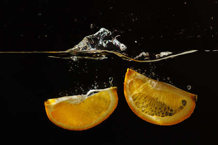 Segments of fresh orange falling into the water with a splash on a black background photo