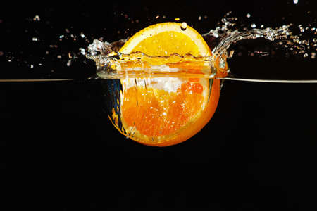 Sliced ripe orange falling into the water with a splash on a dark background  photo
