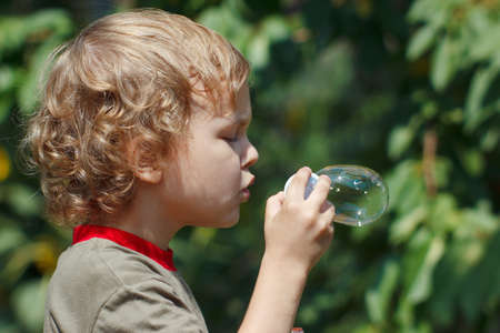 Little boy blowing a bubbles outdoors on a sunny day Stock Photo - 14600352