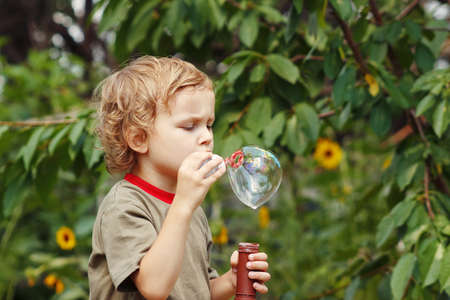 Young blond boy playing with bubbles outdoors on a sunny day photo