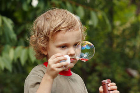Little blond boy playing with bubbles outdoors  photo