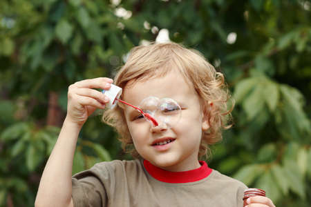 Little boy playing with bubbles outdoors  photo