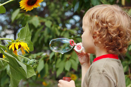 Young blond boy blowing a bubbles outdoors on a sunny day photo