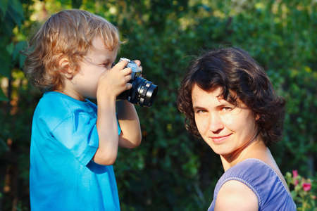 Little blond boy with a camera shoots her mother outdoors photo