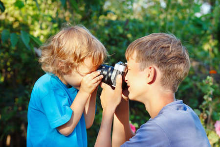 Young beautiful photographers with a camera outdoors photo