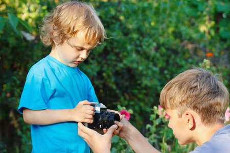 Young blond brothers with a camera outdoors photo