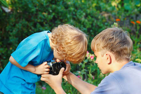 Young blond photographers with a camera outdoors photo
