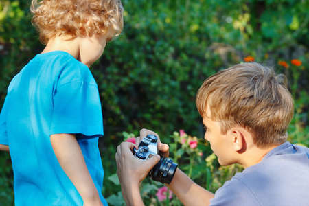 Young cute photographers with a camera outdoors photo