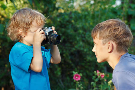 Little cute blond boy with a camera shoots her brother outdoors photo