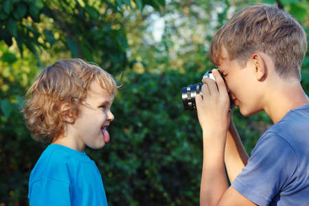 Young photographer with a camera shoots her brother outdoors photo