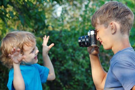 Young blond boy with a camera shoots her brother outdoors photo