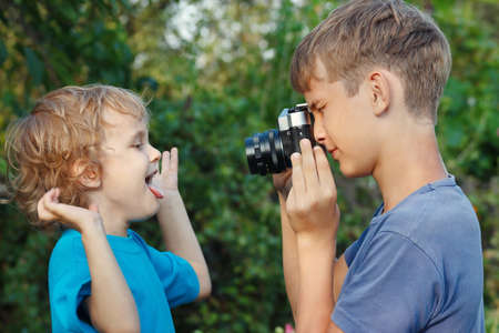 Young photographer with a camera shoots her little brother outdoors photo