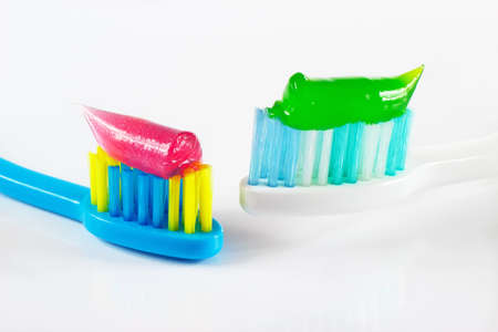 White and blue toothbrushes with pink and green toothpaste on white background Stock Photo