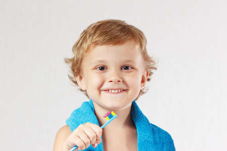 Young cute blond boy with toothbrush with pink toothpaste on a white background