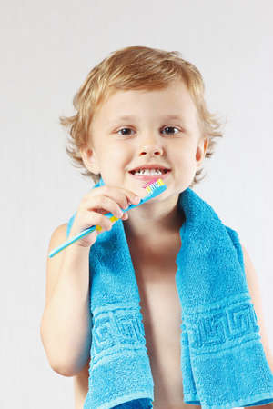Little boy with toothbrush with pink toothpaste on a white background photo