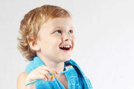 fluoride: Peque�o muchacho rubio lindo cepillarse los dientes en un fondo blanco