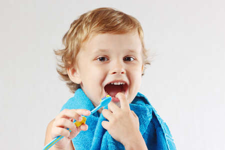 Little cute boy with toothbrush with pink toothpaste on a white background