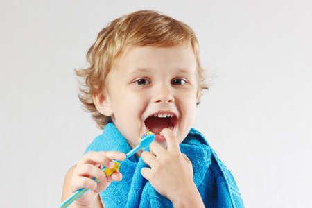 fluoride: Ni�o peque�o lindo con el cepillo de dientes con pasta de dientes de color rosa sobre fondo blanco Foto de archivo