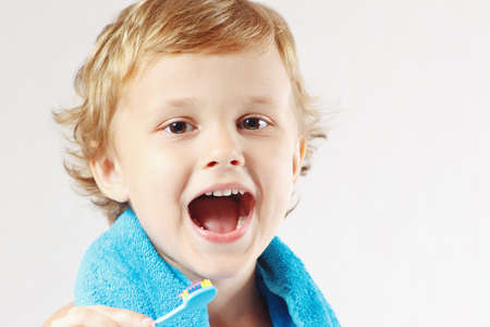 Young cute boy brushing his teeth on a white background photo