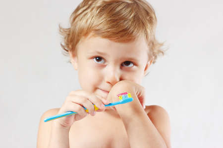 Little cute blond boy with toothbrush with pink toothpaste on a white background photo