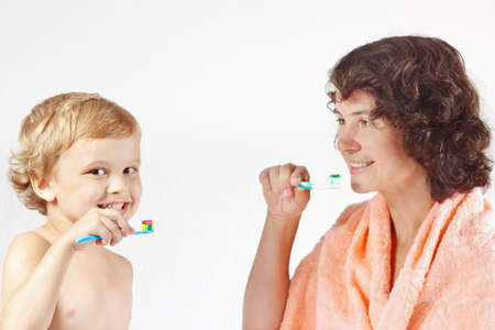 Mother teaches her child to brush their teeth on a white background photo
