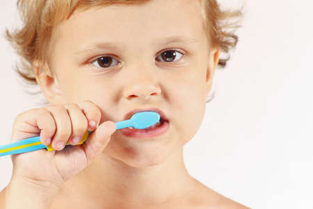 Little cute boy brushing his teeth on a white background photo