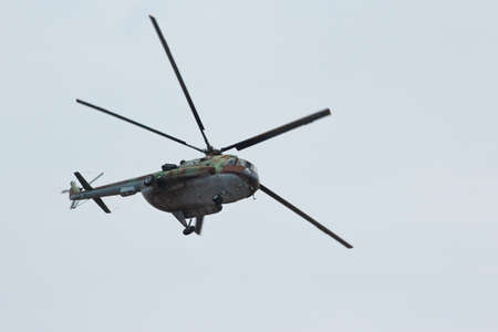 Russian flying military transport helicopter MI-8 make virage in the cloudy sky