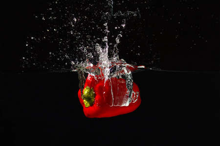 Ripe red bellpepper falling into the water with a splash on a black background photo