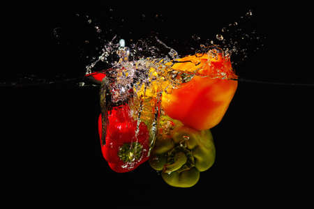 Fresh red, green and yellow bellpepper falling into the water with a splash on a black background photo