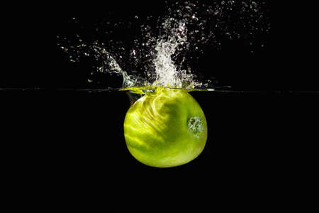 Fresh green apple falling into the water with a splash on a black background closeup photo