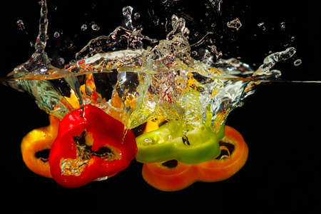 Slices of ripe red, green and yellow pepper falling into the water with a splash on black background  Stock Photo