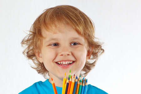 Little smiling boy with color pencils on a white background photo