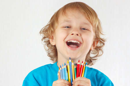 Little cute blond boy holds color pencils on a white background photo