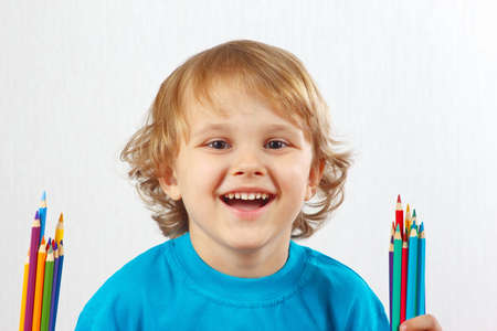 Young cute boy with color pencils on a white background photo