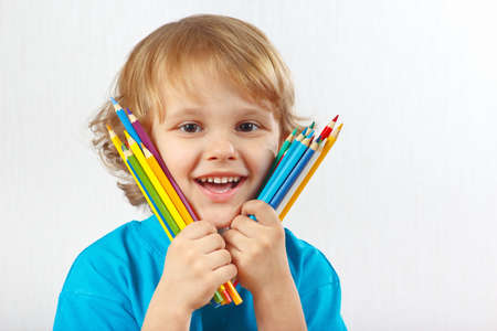 Little smiling boy holds color pencils on a white background photo