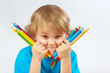Young cute blond boy holds color pencils on a white background photo
