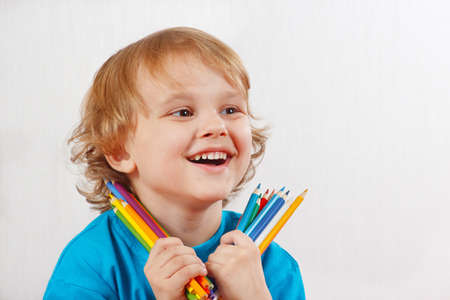 Little blond boy holds color pencils on a white background photo