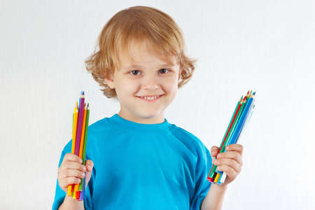 Young blond boy holds color pencils on a white background photo
