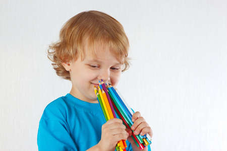 Young cute boy holds color pencils on a white background photo