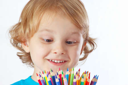 Little cute blond boy looks on color pencils on a white background photo
