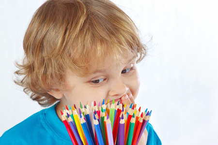 Little cute boy looks on color pencils on a white background photo