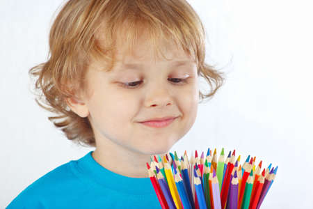 Little blond boy looks on color pencils on a white background photo