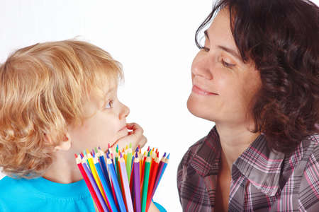 Little blond boy with his mother with color pencils on a white background photo