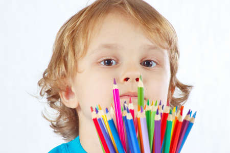 Little cute boy with color pencils on a white background photo