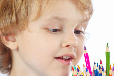 Young blond boy looks on color pencils on a white background photo